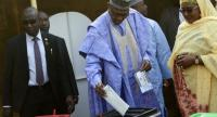 Candidate of the All Progressives Congress (APC) and incumbent President Muhammadu Buhari (C), flanked by his wife Aisha Buhari (R), casts his vote at a polling station in his native hometown Daura in Katsina State, northwest Nigeria, Saturday./FAP