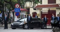 North Korean leader Kim Jong Un's bodyguards stand around his car as he visits the North Korean embassy in Hanoi on February 26.//AFP
