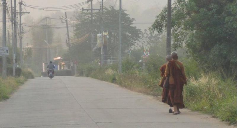 Monks walks through smog in Mae Hong Son's Muang district yesterday to collect morning alms.
