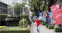 A Thai pedestrian walks past electoral campaign posters installed next to an army tank outside the 2nd Cavalry Division King's Guard in Bangkok, Thailand, 14 February 2019. // EPA-EFE PHOTO