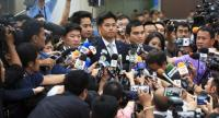 Thai Raksa Chart Party leader Preechaphol Pongpanit is surrounded by journalists at the Constitutional Court yesterday after the dissolution of his party. He and other party executives have been banned from politics for a decade.