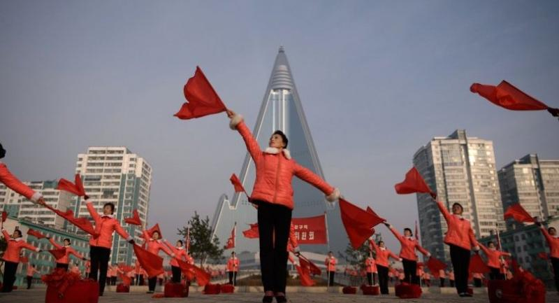 Members of a Socialist Women's Union propaganda troupe perform a dance and music routine in front of the Ryugyong hotel in Pyongyang on March 9, 2019./AFP