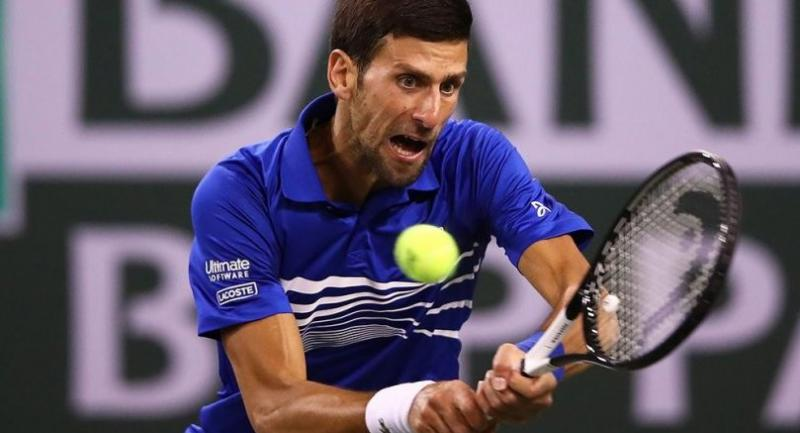 Novak Djokovic of Serbia plays a backhand against Bjorn Fratangelo of the United States. / AFP