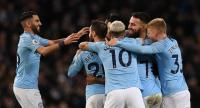Manchester City's English midfielder Raheem Sterling celebrates with teammates. / AFP