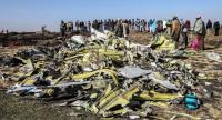 People stand near collected debris at the crash site of an Ethiopian Airlines aircraft near Bishoftu, a town some 60 kilometres southeast of Addis Ababa, on Monday.//AFP