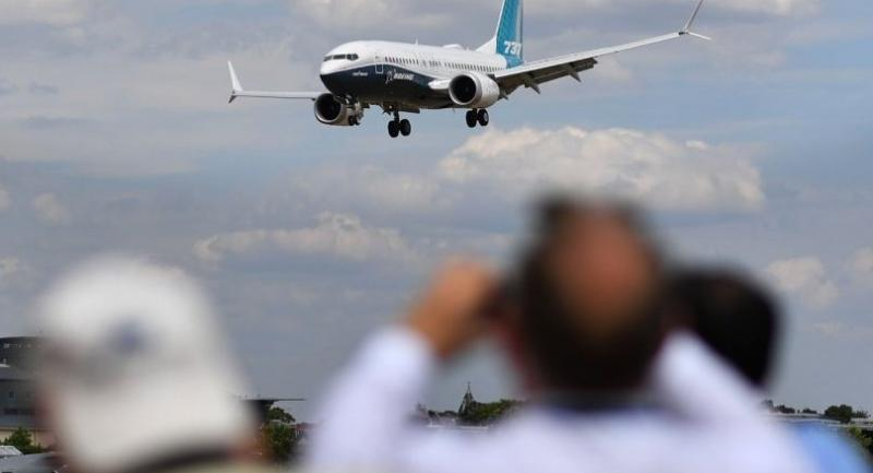 (FILES) In this file photo taken on July 16, 2018 Visitors watch as a Boeing 737 Max lands after an air display during the Farnborough Airshow, south west of London. /AFP