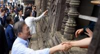 South Korea's President Moon Jae-in (front) and his wife Kim Jung-sook (back C) shake hands with tourists during their visit to the Angkor Wat temple in Siem Reap province on March 16.//AFP