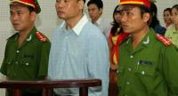 In this file photo taken on March 4, 2014 blogger Truong Duy Nhat (C) stands trial at a local People's Court in the central city of Da Nang.//AFP