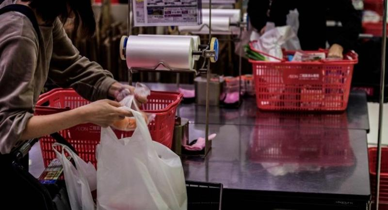 Shoppers pack their purchases into several bags – all of them plastic. /AFP Photo