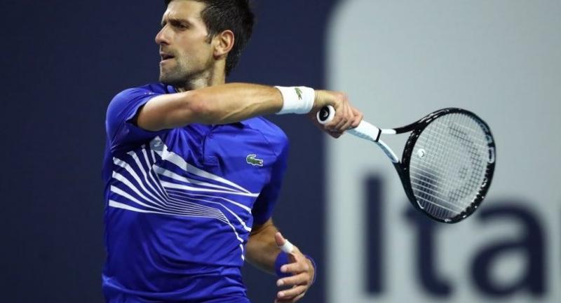 Novak Djokovic of Serbia in action against Bernard Tomic of Australia. / AFP