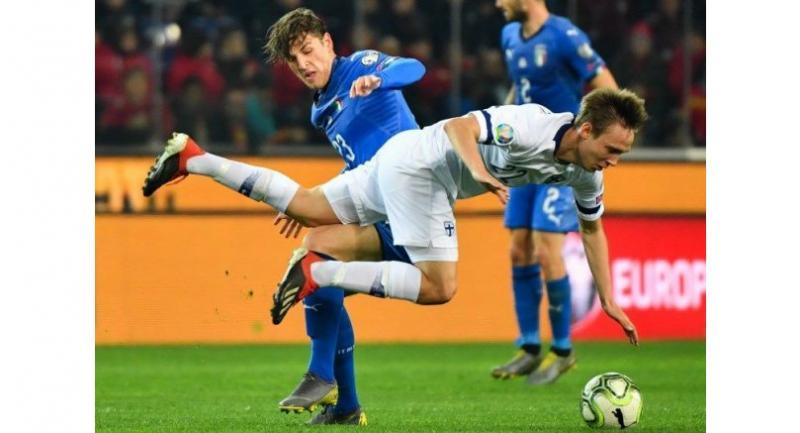 Italy's midfielder Nicolo Zaniolo (L) tackles Finland's forward Lassi Lappalainen during the Euro 2020 Group J qualifying football match between Italy and Finland. / AFP