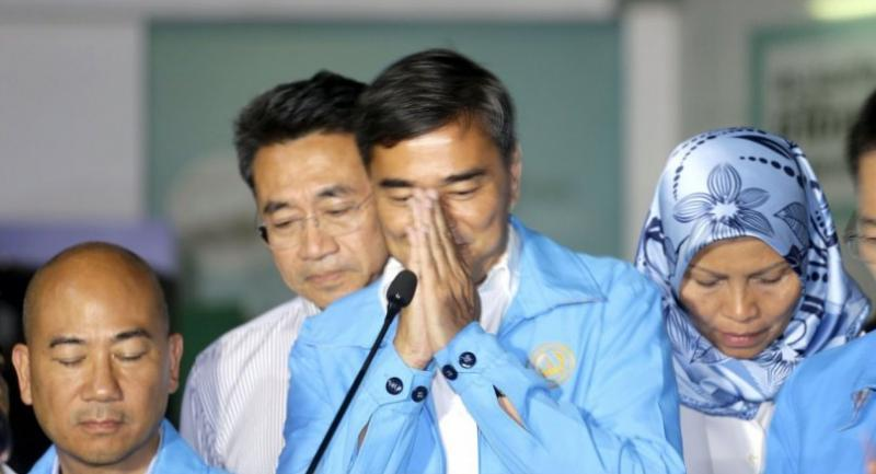 """Abhisit Vejjajiva performs a """"wai"""" as he announces his resignation as leader of the Democrat Party, taking responsibility for the party's electoral defeat."""