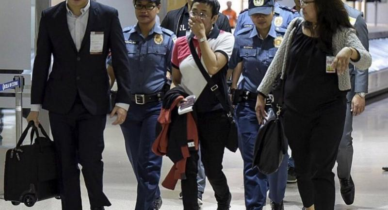 A handout picture made available by the Rappler shows Maria Ressa (C), CEO and Executive Editor of online news site Rappler and President of Rappler Holdings Corporation, being escorted by policemen at an airport in Manila.//EPA-EFE