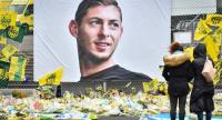 This file photo shows people look at yellow flowers displayed in front of the portrait of Argentinian forward Emiliano Sala at the Beauvoir stadium in Nantes.//AFP