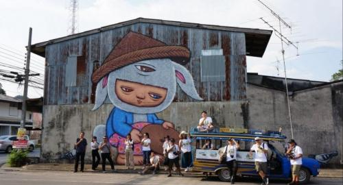 Travellers take photos in front of a mural painted by Alex Face and explore the city of Phang Nga in a song thaew, the local distinctive taxi.
