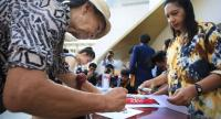 A woman signs a petition in a campaign led by a group of activists to dissolve the Election Commission at Bangkok Art and Culture Centre on April 5.