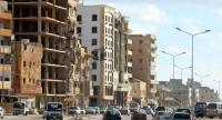 Cars drive past heavily damaged buildings in Libya's eastern city of Benghazi on April 8.//AFP