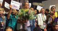 Decha Siriphat, centre,is greeted by his supports at Don Meuang Airport upon arrival from Laos yesterday .Photo by  Pratch Rujivanarom
