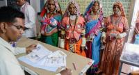 An official checks the names of Indian lambadi tribeswomen at a polling station during India's general election at Pedda Shapur village on the outskirts of Hyderabad on April 11.//AFP