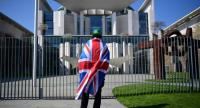A man wearing Britain's Union Flag around his shoulders stands in front of the chancellery during a visit of British Prime Minister May in Berlin, Germany on April 9.//EPA-EFE