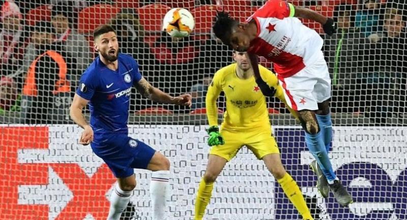 Slavia Prague's Ivorian defender Simon Deli heads the ball clear away from Chelsea's French striker Olivier Giroud (L). / AFP