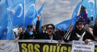 File photo : Protesters of the French Uyghur Community shout slogans of East Turkestan (Uighur flags) during a  protest over China's human rights record  in Paris on March 25, during a state visit of the Chinese president.//AFP