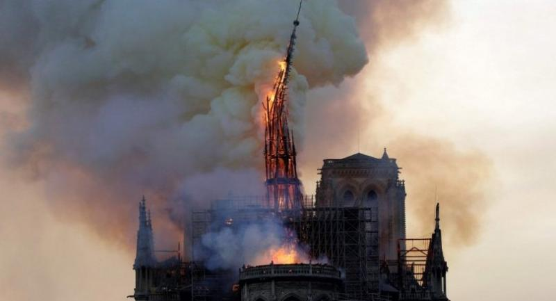 The steeple of the landmark Notre-Dame Cathedral collapses as the cathedral is engulfed in flames in central Paris on April 15, 2019. /AFP
