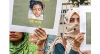 In this photo taken on April 12, Bangladeshi women hold placards and photographs of schoolgirl Nusrat Jahan Rafi at a protest in Dhaka, following her murder by being set on fire after she had reported a sexual assault.//AFP