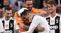 Juventus' Portuguese forward Cristiano Ronaldo (C), his hair covered in foam, and Juventus' Italian goalkeeper Carlo Pinsoglio embrace as they celebrate after Juventus secured its 8th consecutive Italian 2018/19