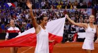 France's Kristina Mladenovic (R) and Caroline Garcia celebrate after winning the fifth rubber. / AFP