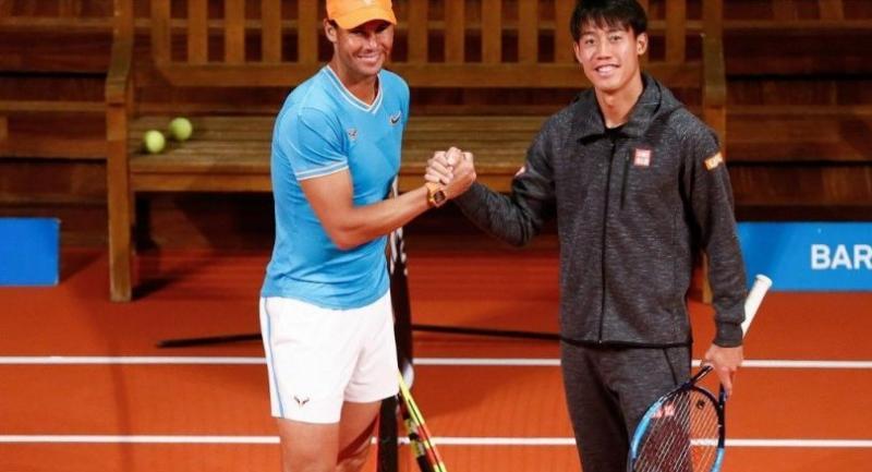 Spain's Rafael Nadal (L) shakes hands with Japan's Kei Nishikori at the Palau de la Musica in Barcelona on April 22, 2019. / AFP