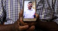 In this photo taken on April 26, 2019, Velusami Raju, father of the Zion Church suicide blast victim Ramesh Raju, shows a photo of his son on a mobile phone at his house, in Kattankudy.//AFP