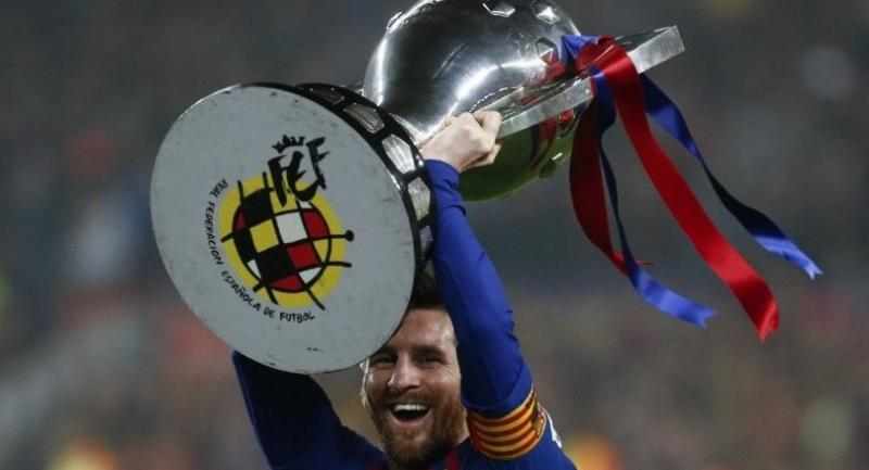 Lionel Messi celebrates with the Liga trophy as Barcelona won their 26th league title after the Spanish League football match between Barcelona and Levante at the Camp Nou stadium in Barcelona.