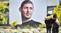 File photo: In this file photo taken on February 8, 2019 people look at yellow flowers displayed in front of the portrait of Argentinian forward Emiliano Sala at the Beauvoir stadium in Nantes. // AFP PHOTO