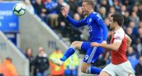 Leicester City's English striker Jamie Vardy (L) lobs the ball over the goalkeeper to hit the bar and score their second goal from the rebound. / AFP