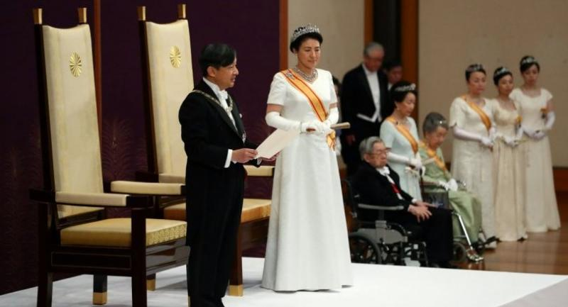 Japan's new Emperor Naruhito delivers his speech as new Empress Masako stands next to him during a ceremony to receive the first audience after the accession to the throne at the Matsu-no-Ma state room inside the Imperial Palace in Tokyo .//AFP
