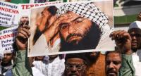 Protesters hold a scratched photo of Jaish-e-Mohammad group chief, Maulana Masood Azhar, as they shout slogans against Pakistan.//AFP