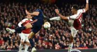 Arsenal's Gabonese striker Pierre-Emerick Aubameyang (R) cannot connect with this ball as Valencia's Brazilian defender Gabriel Paulista (L). / AFP