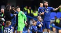 Chelsea's French striker Olivier Giroud waves to fans as he walks with his family following the English Premier League football match between Chelsea and Watford. / AFP