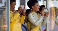 This handout from Royal Household Bureau shows Princess Sirivannavari Nariratana (R) watching the coronation procession of her father King Maha Vajiralongkorn with the king's sister Princess Sirindhorn on May 5.//AFP