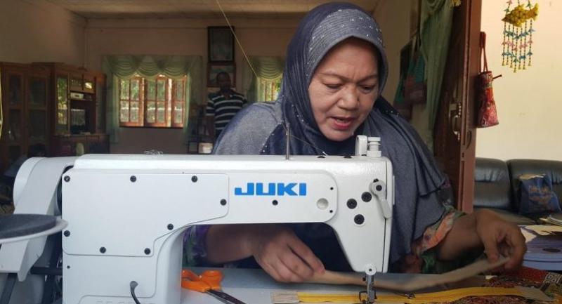 Rattana Duereso sews a bag at her house in Pattani's Muang district./Photo by Jintana Panyaarvudh