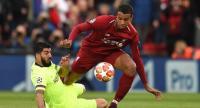 Barcelona's Uruguayan striker Luis Suarez (L) tackles Liverpool's German-born Cameroonian defender Joel Matip./ AFP