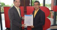Narupon Rattanasamaharn, right, Dtac's senior vice president, presents the company's expression of interest to NBTC deputy secretary-general Korkij Danchaivichit on Friday.