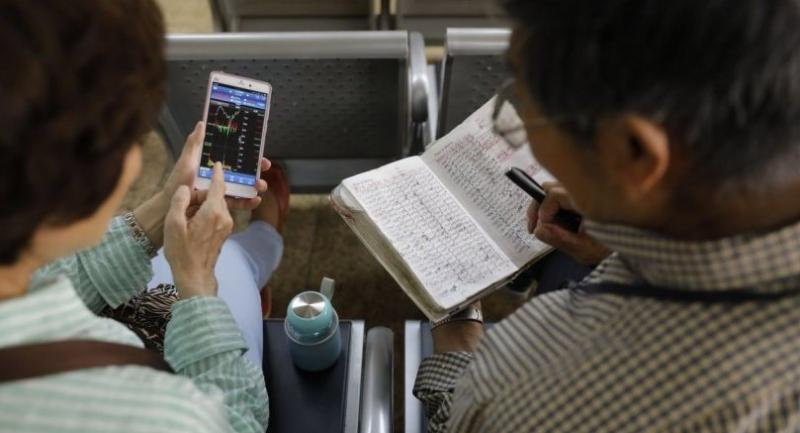 A Chinese investor checks the stock prices records on his notebook while another investor views the stock composite index on her mobile phone at a securities brokerage house in Beijing, China on May 10.//EPA-EFE