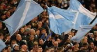 Manchester City fans wave flags.