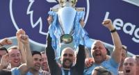 Manchester City's Spanish manager Pep Guardiola holds up the Premier League trophy as he's surrounded by his staff after their 4-1 victory in the English Premier League football match between Brighton and Hove Albion and Manchester City. / AFP