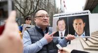 This file photo shows Louis Huang of Vancouver Freedom and Democracy for China holding photos of Canadians Michael Spavor and Michael Kovrig, who are being detained by China, in Vancouver.//AFP