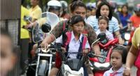 Neither parents nor their children wear helmets as they make their way to Na Luang School in Bangkok's Thung Khru district yesterday. The school has more than 3,000 students.