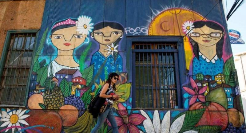 A woman walks past a street mural in Valparaiso./AFP