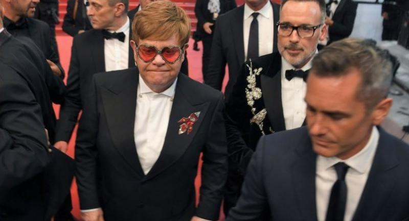 British singer-songwriter Elton John (L) and his husband Canadian filmmaker David Furnish (Rear R) leave following the screening of the film